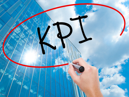 Man Hand writing KPI (Key Performance Indicator) with black marker on visual screen.  Business, technology, internet concept. Modern business skyscrapers background. Stock Photo