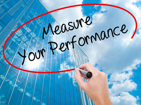 Man Hand writing Measure Your Performance with black marker on visual screen. Business, technology, internet concept. Modern business skyscrapers background. Stock Photo