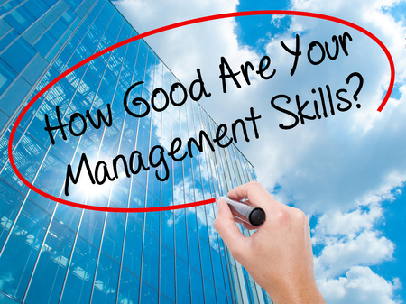 Man Hand writing How Good Are Your Management Skills? with black marker on visual screen. Business, technology, internet concept. Modern business skyscrapers background. Stock Photo