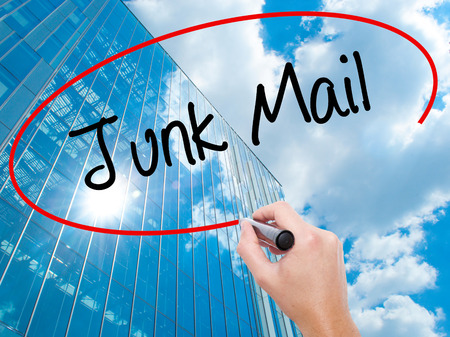 solicitors: Man Hand writing Junk Mail with black marker on visual screen. Business, technology, internet concept. Modern business skyscrapers background. Stock Photo