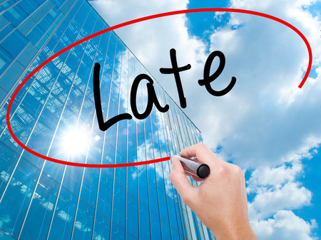 lateness: Man Hand writing Late with black marker on visual screen.  Business, technology, internet concept. Modern business skyscrapers background. Stock Photo