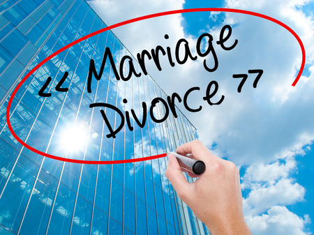 severance: Man Hand writing Marriage - Divorce with black marker on visual screen.  Business, technology, internet concept. Modern business skyscrapers background. Stock Photo
