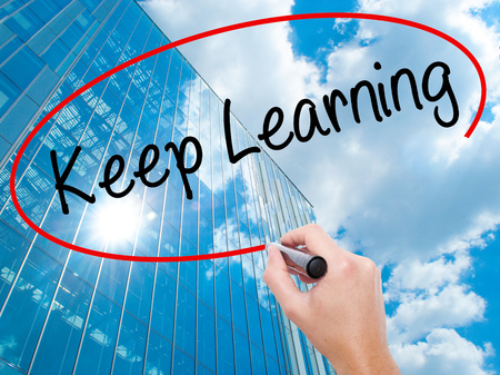 Man Hand writing Keep Learning with black marker on visual screen. Business, technology, internet concept. Modern business skyscrapers background. Stock Photo Stock Photo