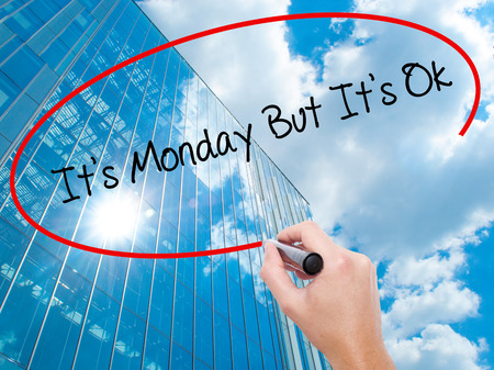 Man Hand writing Its Monday But Its Ok with black marker on visual screen. Business, technology, internet concept. Modern business skyscrapers background. Stock Photo