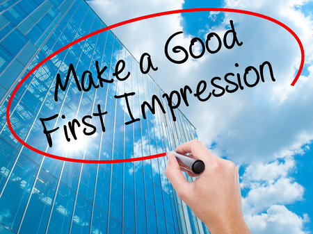 pioneering: Man Hand writing Make a Good First Impression with black marker on visual screen.  Business, technology, internet concept. Modern business skyscrapers background. Stock Photo Stock Photo
