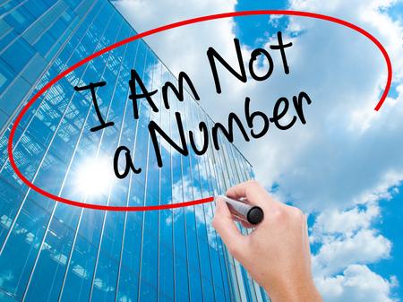 Mano de hombre escribiendo No soy un número con marcador negro en la pantalla visual. Negocios, tecnología, concepto de internet. Fondo de rascacielos de negocios modernos. Foto de stock