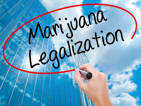 legislators: Man Hand writing Marijuana Legalization with black marker on visual screen. Live, technology, internet concept. Modern business skyscrapers background. Stock Photo