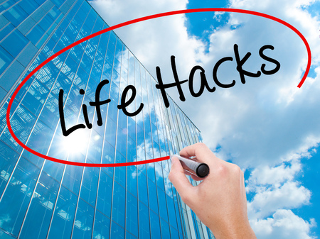 Man Hand writing Life Hacks with black marker on visual screen.  Business, technology, internet concept. Modern business skyscrapers background. Stock Photo Stock Photo