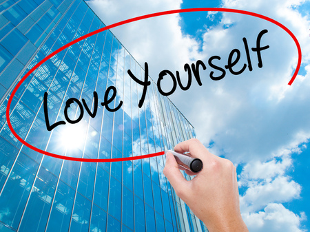 egoistic: Man Hand writing Love Yourself with black marker on visual screen. Business, technology, internet concept. Modern business skyscrapers background. Stock Photo