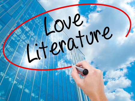 Man Hand writing Love Literature with black marker on visual screen.  Business, technology, internet concept. Modern business skyscrapers background. Stock Photo