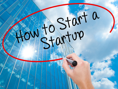 Man Hand writing How to Start a Startup with black marker on visual screen.  Business, technology, internet concept. Modern business skyscrapers background. Stock Photo Stock Photo