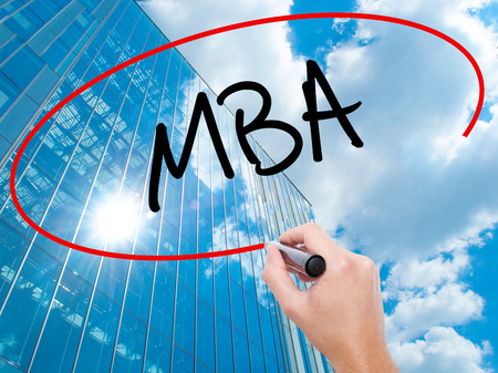 Man Hand writing MBA with black marker on visual screen.  Business, technology, internet concept. Modern business skyscrapers background. Stock Photo