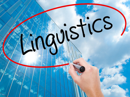 Man Hand writing Linguistics  with black marker on visual screen.  Business,  technology, internet concept. Modern business skyscrapers background. Stock Photo Reklamní fotografie