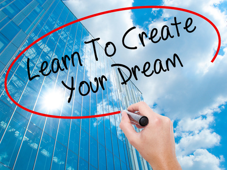 Man Hand writing Learn To Create Your Dream with black marker on visual screen.  Business, technology, internet concept. Modern business skyscrapers background. Stock Photo