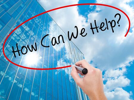 can we help: Man Hand writing How Can We Help? with black marker on visual screen.  Business, technology, internet concept. Modern business skyscrapers background. Stock Photo