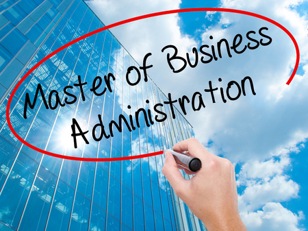 Man Hand writing Master of Business Administration with black marker on visual screen. Business, technology, internet concept. Modern business skyscrapers background. Stock Photo