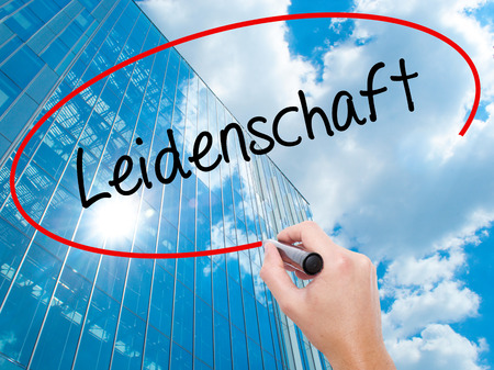 Man Hand writing Leidenschaft (Passion in German)  with black marker on visual screen. Business, technology, internet concept. Modern business skyscrapers background. Stock Photo