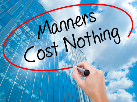 Man Hand writing Manners Cost Nothing with black marker on visual screen. Business, technology, internet concept. Modern business skyscrapers background. Stock Photo