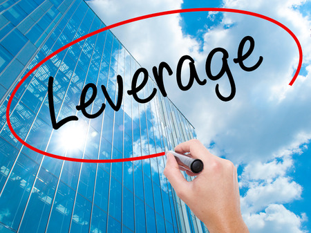 Man Hand writing Leverage with black marker on visual screen.  Business, technology, internet concept. Modern business skyscrapers background. Stock Photo