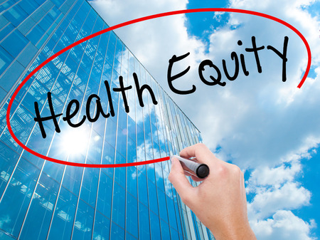 Man Hand writing Health Equityt with black marker on visual screen. Business, technology, internet concept. Modern business skyscrapers background. Stock Photo