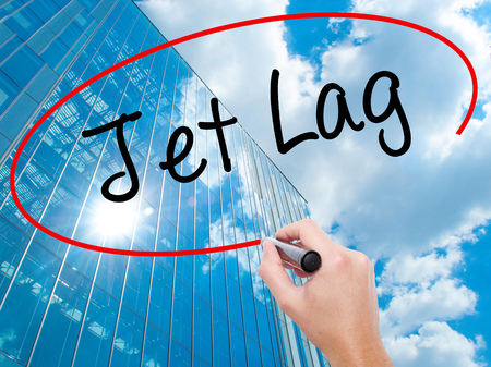 Man Hand writing  Jet Lag with black marker on visual screen.  Business, technology, internet concept. Modern business skyscrapers background. Stock Photo