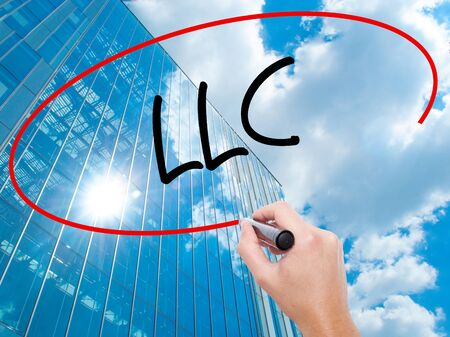 Man Hand writing  LLC (Limited Liability Company)  with black marker on visual screen.  Business, technology, internet concept. Modern business skyscrapers background. Stock Photo
