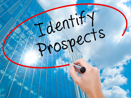 Man Hand writing Identify Prospects with black marker on visual screen. Business, technology, internet concept. Modern business skyscrapers background. Stock Photo