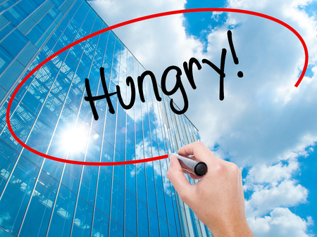 Man Hand writing Hungry! with black marker on visual screen. Business, technology, internet concept. Modern business skyscrapers background. Stock Photo