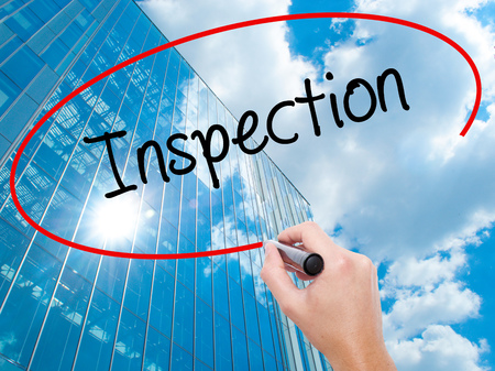 warranty questions: Man Hand writing Inspection with black marker on visual screen. Business, technology, internet concept. Modern business skyscrapers background. Stock Photo