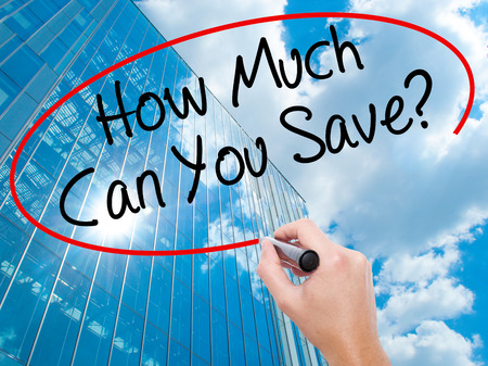 mortgaging: Man Hand writing How Much Can You Save? with black marker on visual screen. Business, technology, internet concept. Modern business skyscrapers background. Stock Photo