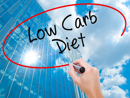 Man Hand writing Low Carb Diet with black marker on visual screen. Business, technology, internet concept. Modern business skyscrapers background. Stock Photo