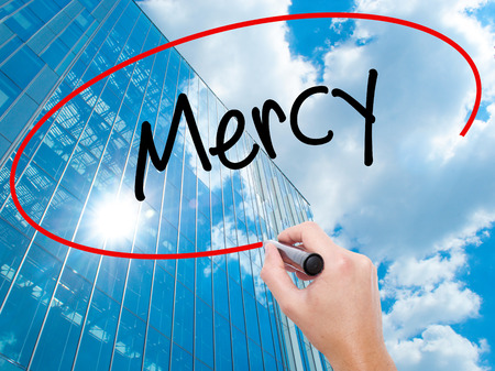Man Hand writing Mercy with black marker on visual screen. Business, technology, internet concept. Modern business skyscrapers background. Stock Photo