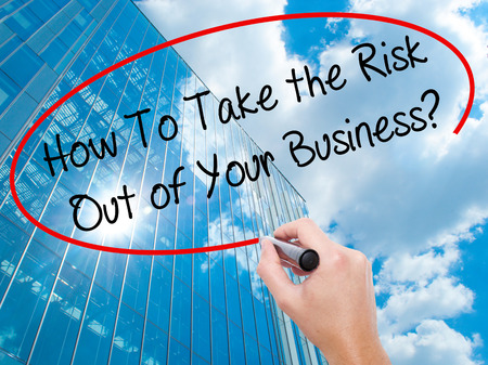 Man Hand writing How To Take the Risk Out of Your Business? with black marker on visual screen. Business, technology, internet concept. Modern business skyscrapers background. Stock Photo