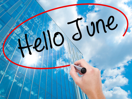 Man Hand writing Hello June  with black marker on visual screen. Business, technology, internet concept. Modern business skyscrapers background. Stock Photo
