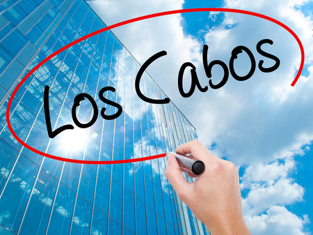 Man Hand writing Los Cabos with black marker on visual screen. Business, technology, internet concept. Modern business skyscrapers background. Stock Photo Stock Photo