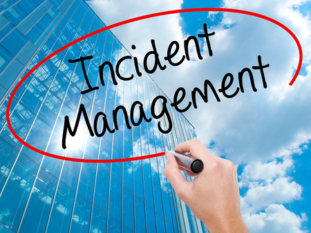 Man Hand writing Incident Management with black marker on visual screen. Business, technology, internet concept. Modern business skyscrapers background. Stock Photo