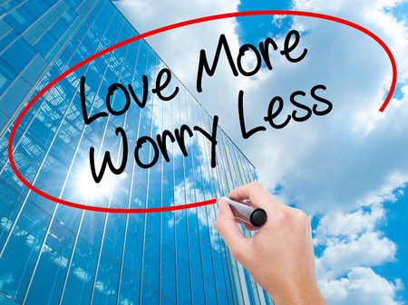 Man Hand writing Love More Worry Less with black marker on visual screen.  Business, technology, internet concept. Modern business skyscrapers background. Stock Photo