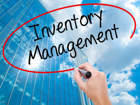 Man Hand writing Inventory Management with black marker on visual screen.  Business, technology, internet concept. Modern business skyscrapers background. Stock Photo