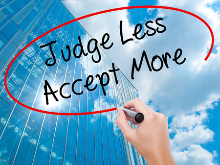 Man Hand writing Judge Less Accept More with black marker on visual screen.  Business, technology, internet concept. Modern business skyscrapers background. Stock Photo