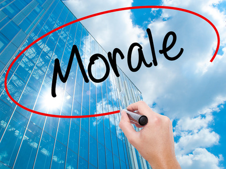 morale: Man Hand writing Morale with black marker on visual screen. Business, technology, internet concept. Modern business skyscrapers background. Stock Photo