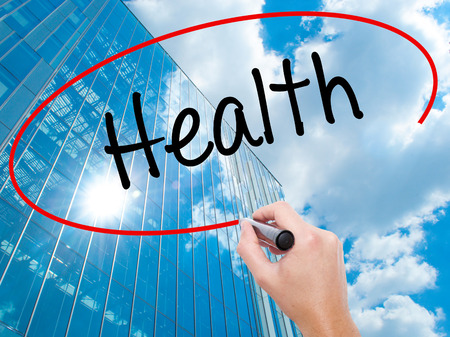 buena postura: Man Hand writing Health with black marker on visual screen. Business, technology, internet concept. Modern business skyscrapers background. Stock Photo