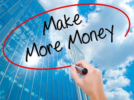 Man Hand writing Make Money Money  with black marker on visual screen.  Business, technology, internet concept. Modern business skyscrapers background. Stock Photo
