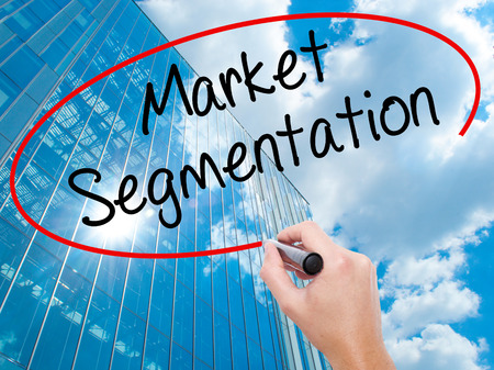 Man Hand writing Market Segmentation with black marker on visual screen.  Business, technology, internet concept. Modern business skyscrapers background. Stock Photo