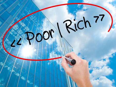 Man Hand writing Poor - Rich with black marker on visual screen.  Business, technology, internet concept. Modern business skyscrapers background. Stock Photo