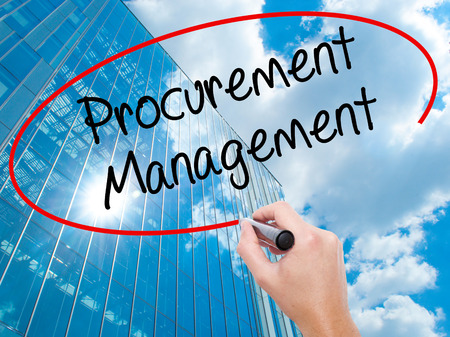 Man Hand writing Procurement Management with black marker on visual screen.  Business, technology, internet concept. Modern business skyscrapers background. Stock Photo