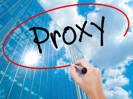 Man Hand writing Proxy with black marker on visual screen.  Business, technology, internet concept. Modern business skyscrapers background. Stock Photo