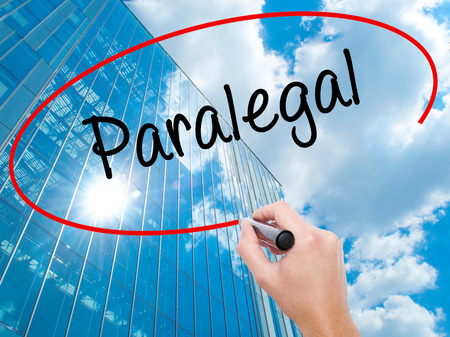 paralegal: Man Hand writing Paralegal with black marker on visual screen. Business, technology, internet concept. Modern business skyscrapers background. Stock Photo