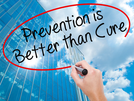 cure prevention: Man Hand writing Prevention is Better than Cure with black marker on visual screen. Business, technology, internet concept. Modern business skyscrapers background. Stock Image