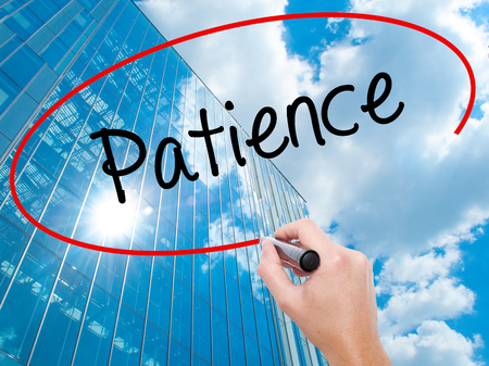 Man Hand writing Patience with black marker on visual screen.  Business, technology, internet concept. Modern business skyscrapers background. Stock Photo Stock Photo