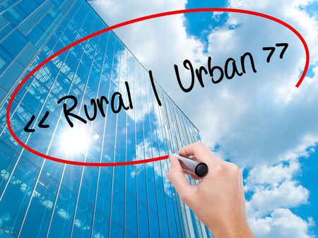 Man Hand writing Rural - Urban with black marker on visual screen.  Business, technology, internet concept. Modern business skyscrapers background. Stock Photo